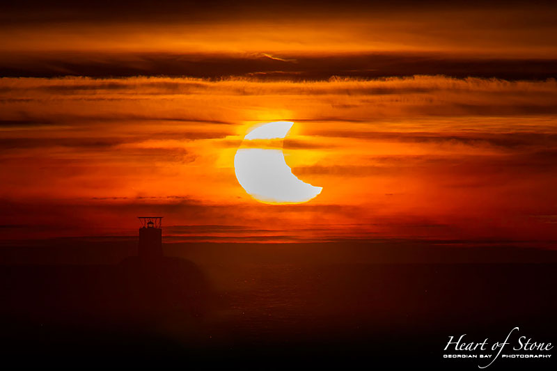 Partial solar eclipse over Red Rock lighthouse, Parry Sound, Georgian Bay