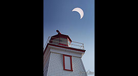 Solar eclipse of 2017 over lantern room of lighthouse, Gereaux Island, Georgian Bay